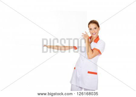 Happy female doctor or nurse holding empty banner