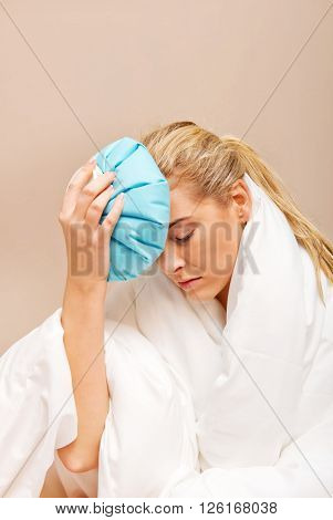 Young woman with headache, holding an ice-bag next to her forhead