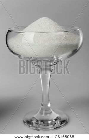 Margarita glass filled with granulated sugar on grey background