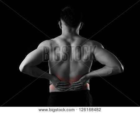 young muscular body sport man holding sore low back waist with his hands suffering pain in athlete stress and health care concept isolated black and white red spot injury
