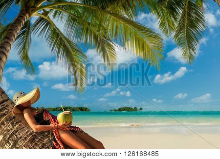 Woman sitting on a coconut tree on Phi Phi island in Thailand
