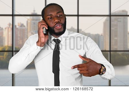 Darkskinned man on the phone. Manager's phonetalk in the city. Diplomacy is priceless. Honest and trustworthy leader.