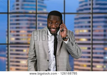 Elated african man holding cellphone. Smiling topmanager on evening background. Satisfied with new results. Things couldn't get better.