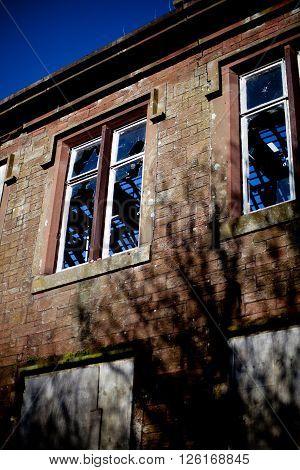 Derelict sandstone building with broken windows and boarded up doors