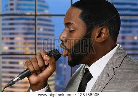 Afro singer with microphone. Singing male on skyscraper background. Recording studio in high building. New single from upcoming album.