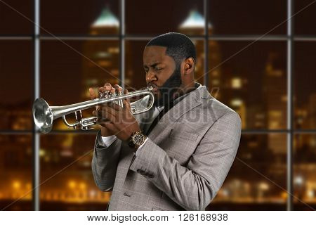Black man plays the trumpet. Jazz trumpeter on night background. Composer's outstanding trumpet solo. Musician and instrument are one.