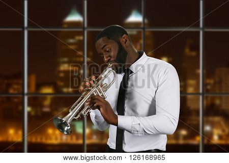 Darkskinned trumpeter in white shirt. Trumpeter on night city background. Enthusiastic and talented man. Music flows through him.