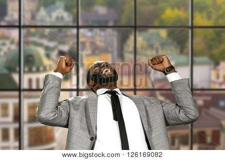 Afro businessman expressing joy. Victorious man on urban background. Sweet moment of joy. Happy and fearless.