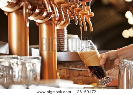 Barman hand pouring a lager beer in a glass.