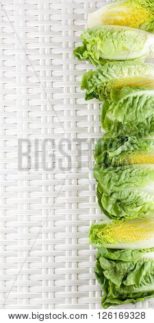 Frame of Fresh Crunchy Romaine Lettuce Full Heads and Halves with Water Drops closeup on Wicker background