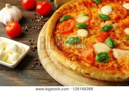 Margherita pizza with tomatoes, garlic, spices and Mozzarella on wooden background