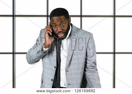 Nervous black businessman holding cellphone. Afro clerk on white background. Unsettling news for company employee. Difficult day at work.