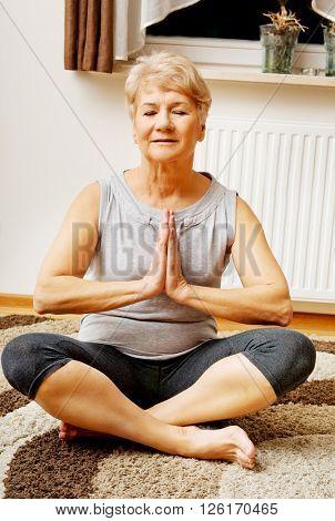 Senior woman doing yoga in living room