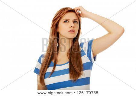 Pensive teenage woman scratching her head