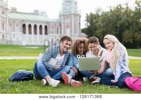 Young students with laptop outdoors