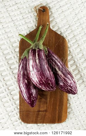 Three Fresh Raw Striped Aubergines on Wooden Cutting Board closeup on Wicker background. Top View