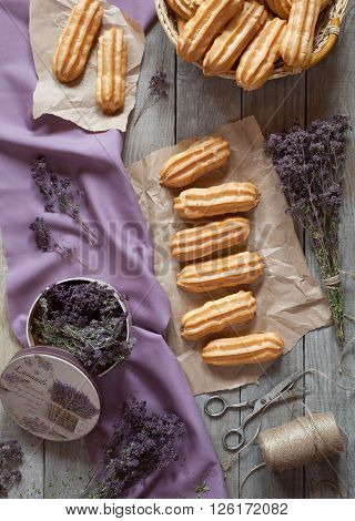 Traditional eclairs or profiterole pastry dessert filled with whipped cream on baking sheet background. Top view, provence rustic style.