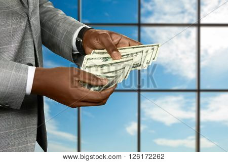 Black businessman's hand counts money. Counting cash on sky background. The fortune in his hands. Enjoy while you can.