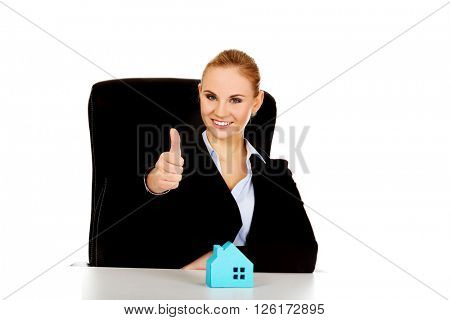 Business woman with blue paper house on the desk shows thumb up