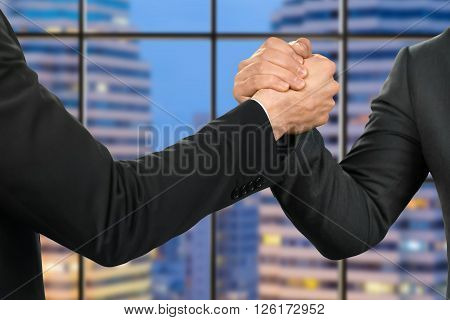 Friendly businessmen shake hands. Partners' handshake on megalopolis background. City waits for its leaders. Confident reliable people.