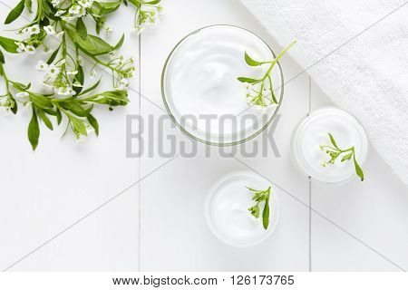 Herbal bodycare cosmetic hygienic cream with flowers skincare product wellness and relaxation medical mask in glass jar on white background