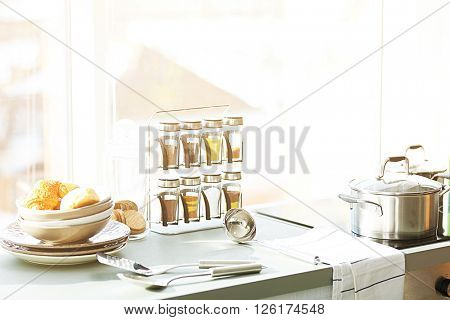 Table with electric stove, utensils and spices in the kitchen beside window