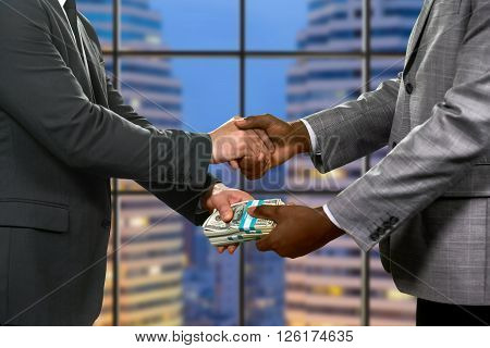 Businessmen's handshake and money transfer. Financial deal beside skyscraper. Simple and effective approach. Be attentive with your partners.