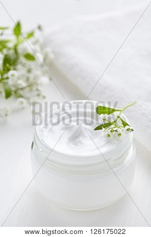 Medical herbal cosmetic cream with flowers hygienic skincare product wellness and relaxation makeup mask in glass jar with towel on white background