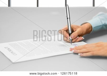Businesswoman's hand signs a document. Signing paper on white background. One step makes many changes. Think before you move on.