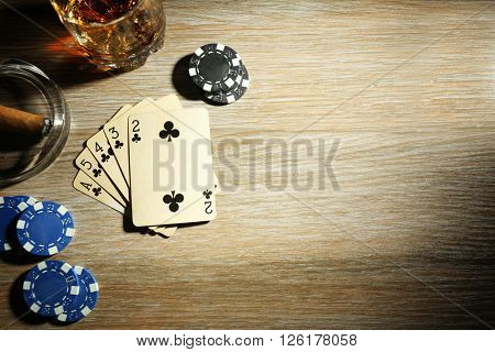Set to playing poker with cards and chips on wooden table, top view