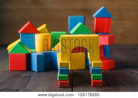 building from wooden colourful childrens blocks on wooden floor