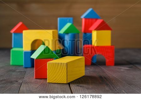 building from wooden colourful childrens blocks on table
