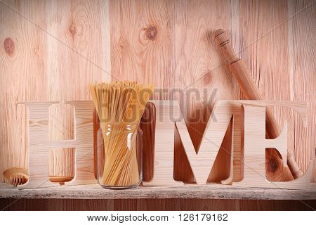 Home word with rolling pin and spaghetti on wooden background
