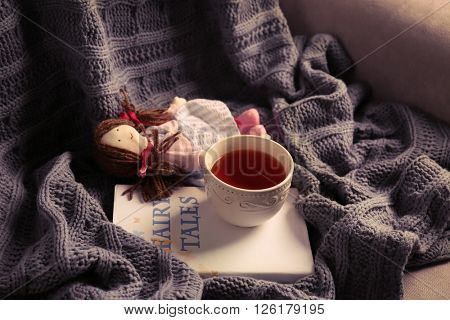Rag doll with fairy tales book and cup of tea on bedspread. Childhood concept