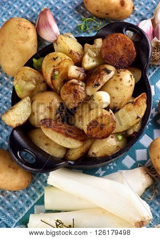 Homemade Roasted Potato Wedges and Halves with Onion and Garlic in Black Cast Iron Pot closeup on Napkin. Top View