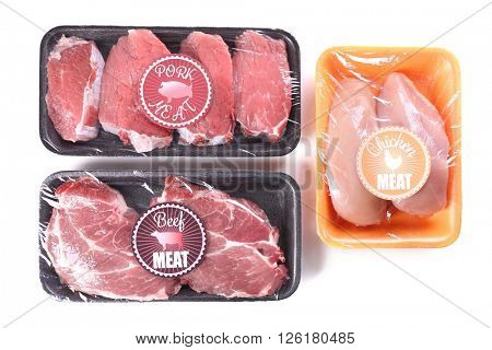 Packed pieces of chicken, pork and beef meat, isolated on white