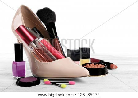 Makeup set with beige woman's shoe, brush and cosmetics on light background