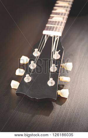 Head stock of electric guitar with tuning pegs on black wooden background