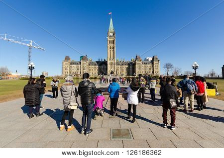 OTTAWA CANADA - April 15 2016: Tourists taking pictures in front of Canadian Parliament in Ottawa.
