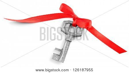 Old key with red bow, isolated on white