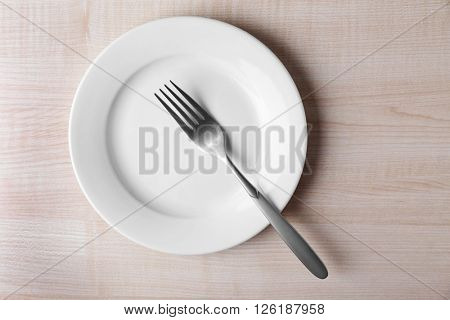 Empty plate with fork on wooden background