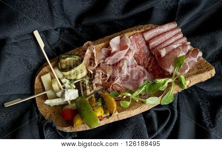 appetizer with salami, prosciutto, muscle, smoked sausage, grilled leg, grilled vegetables and cheese on wooden tray
