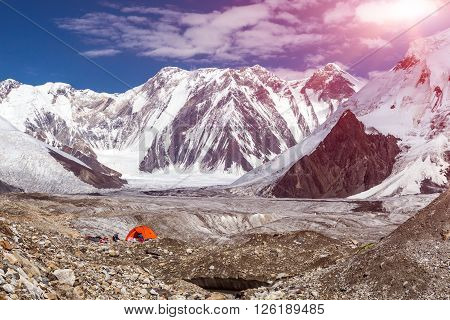 Panorama of High Mountains Range and Red Camping Tent on Glacier Moraine Sun Shining