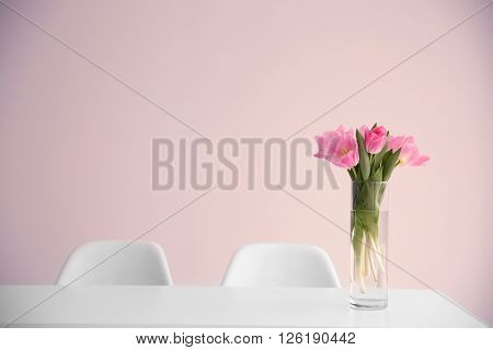 Beautiful tulips on dinning table against white wall background