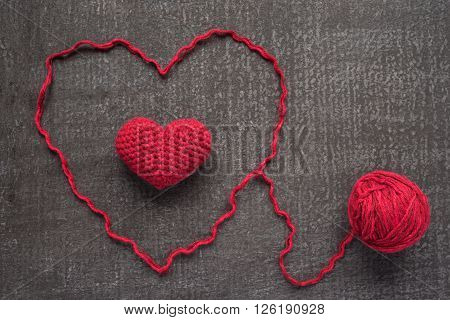 Crocheted red heart on a grunge board with a ball of woolen yarn.