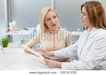 Professional female gynecologist is consulting a young woman. She is holding a paper and pointing finger at it with seriousness. Blond girl is listening to her attentively