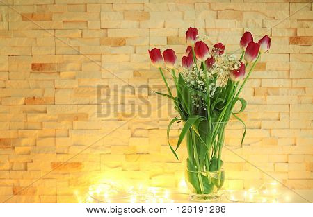 Tulips on the table in front of brick wall background