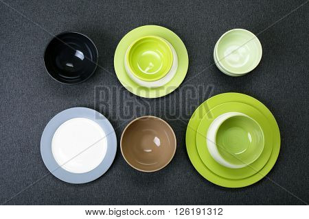 Empty dishes on black wooden background.