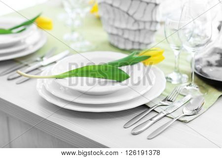 Table served with dishes and a tulips on them
