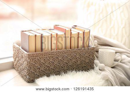 Pile of books in wicker box on windowsill, closeup